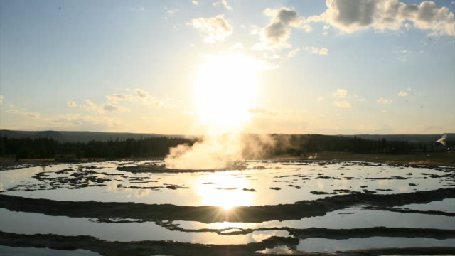 steam erupts from grand fountain geyser as the sun sets behind it. - geyser video stock e b–roll