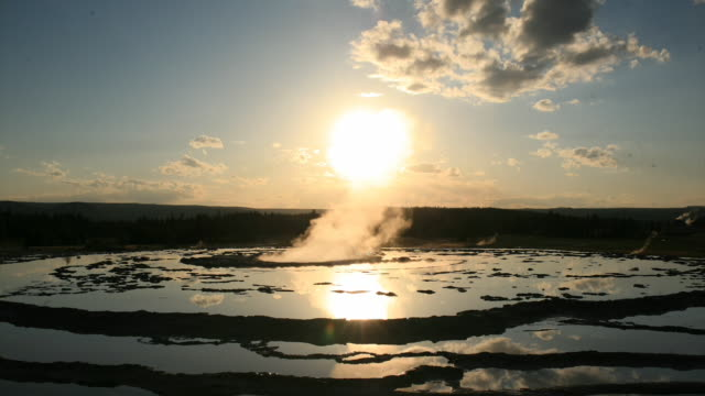 steam erupts from grand fountain geyser in yellowstone national park as the sun sets behind it. - geyser video stock e b–roll
