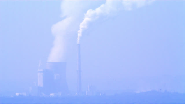 Steam escapes from a cooling tower and smokestack at an industrial plant.