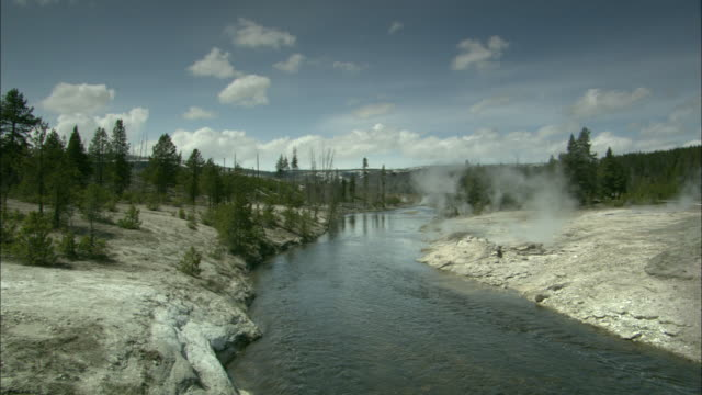 steam escapes from vents along a yellowstone stream. - yellowstone national park stock videos & royalty-free footage
