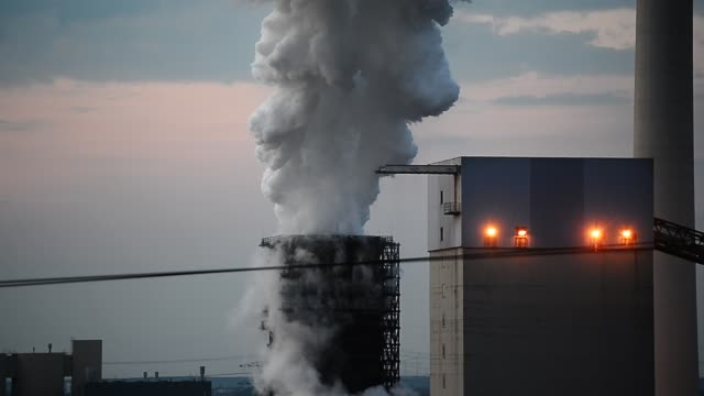 steam from a cooling tower rises up to the sky at thyssenkrupp schwelgern steel plant illuminated at twilight on may 30 2018 in duisburg germany the... - ruhr stock videos & royalty-free footage