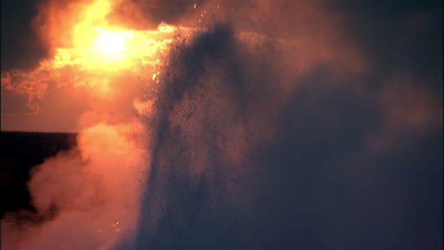 steam from erupting geyser at sunset, yellowstone, usa - geyser stock videos and b-roll footage
