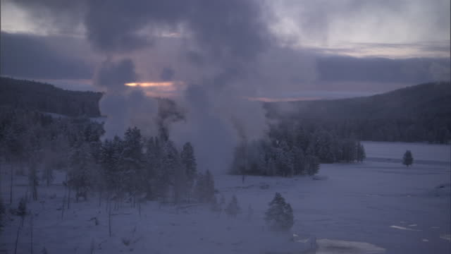 Steam from hot springs rises over snowy forest, Yellowstone, USA