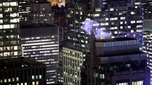 Steam from roof of building in Manhattan at night, New York, United States