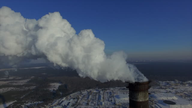 Steam from the 270-meter chimney bright frosty winter day. The rise of the camera along the tube