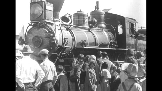 steam locomotive coming into station toward camera / side view locomotive with engineer at window as it passes crowd by tracks / train car with words... - trasporto ferroviario video stock e b–roll