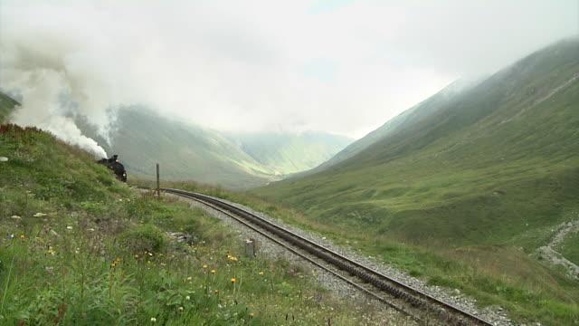 dfb steam locomotive just before entering furka station - zug mit dampflokomotive stock-videos und b-roll-filmmaterial