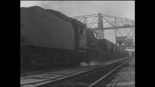 a steam locomotive pulls coal cars on a fukuoka rail line. - breitwandformat stock-videos und b-roll-filmmaterial