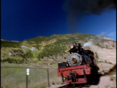 vidéos et rushes de cu, la, steam locomotive travelling through mountain landscape - locomotive