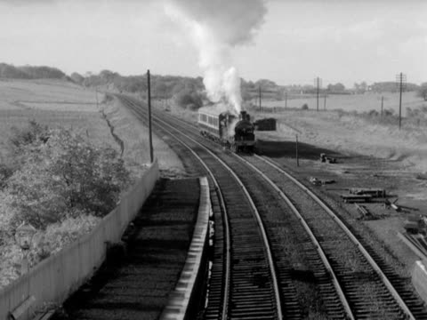 a steam passenger train with two carriages pulls up at a small railway station in the countryside 1965 - steam train stock videos & royalty-free footage