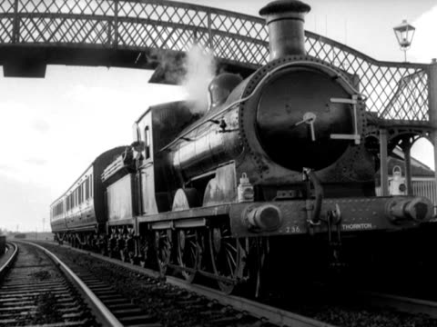 steam passenger train with two carriages stops underneath a pedestrian bridge at a small rural railway station; 1965 - locomotive stock videos & royalty-free footage