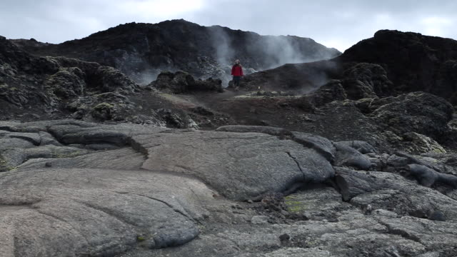 WS Steam pouring out of volcanic black landscape, young woman walking down on volcanic rock at leirhnjukur / Krafla, Myvatn region, Iceland