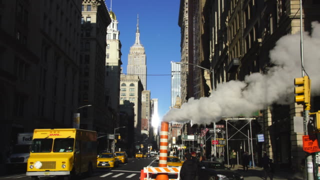 steam rises and drifts among the fifth avenue buildings in the wintertime at midtown manhattan new york city ny usa on jan. 03 2019. - empire state building stock-videos und b-roll-filmmaterial