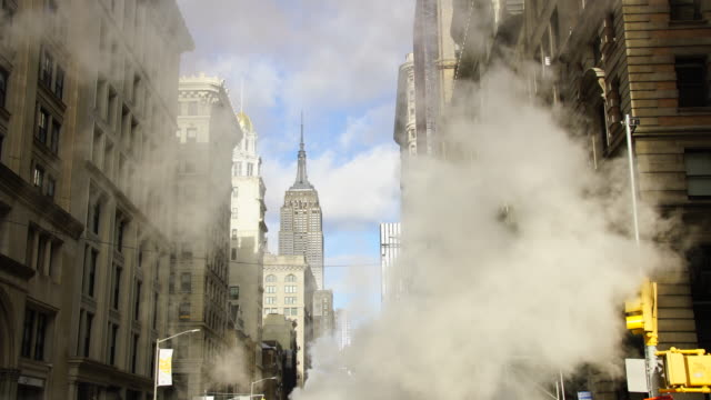 steam rises and drifts among the rows of fifth avenue buildings at front of the empire state building in the wintertime at midtown manhattan new york city ny usa on dec. 26 2018. - gebäudefront stock-videos und b-roll-filmmaterial