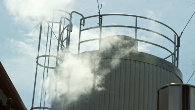 steam rises from a beer fermenter at a manufacturing facility under a sunny, blue sky - storage tank stock videos & royalty-free footage