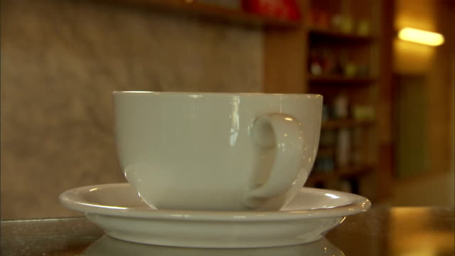 steam rises from a coffee cup on a saucer. - saucer stock videos & royalty-free footage