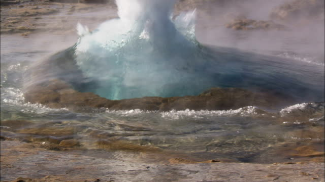 steam rises from a geyser as it erupts into a fountain of water. available in hd. - geyser stock videos & royalty-free footage