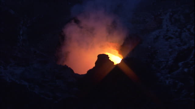 Steam rises from a hole in an active volcano.