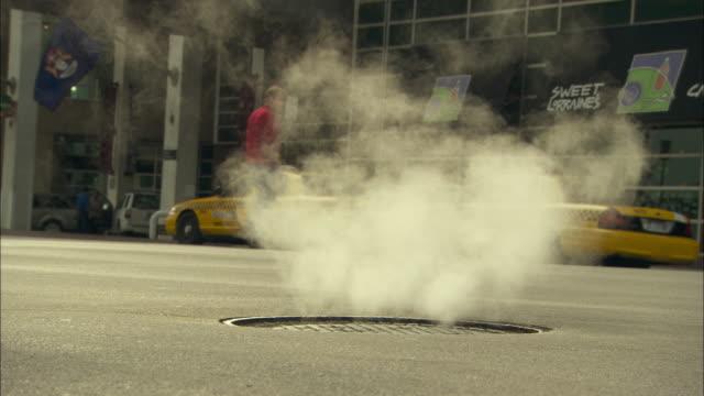 vídeos y material grabado en eventos de stock de steam rises from a manhole in detroit. - tapadera de cloaca