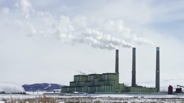 冬の雪の日に、コロラド州クレイグの外の発電所から蒸気が上昇する - 工場の煙突点の映像素材/bロール