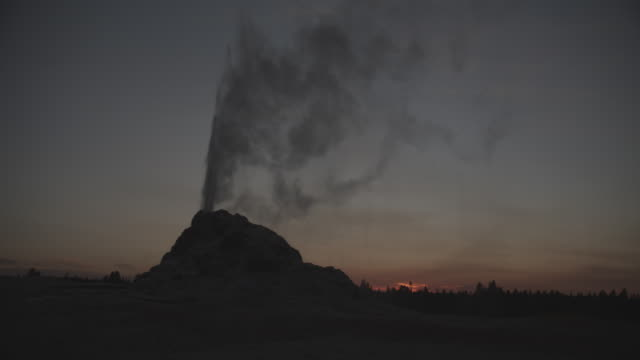 steam rises from a small geyser in yellowstone national park. - geysir stock-videos und b-roll-filmmaterial