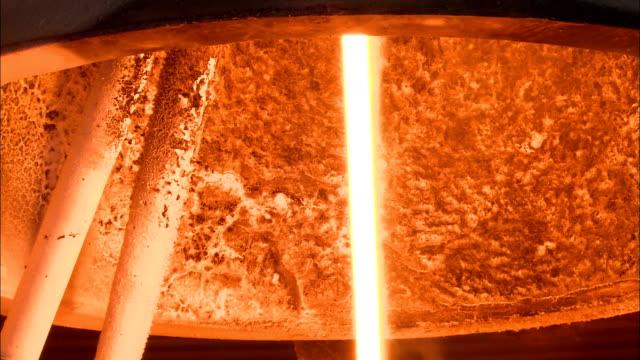 steam rises from a stream of molten glass in a fiberglass factory. - 金属融解点の映像素材/bロール