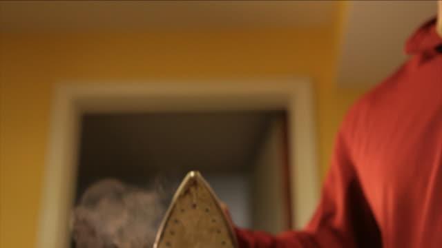 vidéos et rushes de steam rises from an iron as man irons clothing. - fer