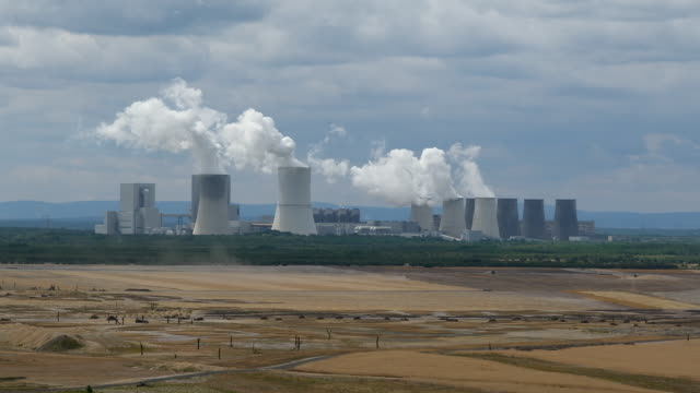 steam rises from cooling towers of the boxberg coalfired power plant next to reconstituted land of the plant's adjacent openpit lignite coal mine on... - 1989 stock-videos und b-roll-filmmaterial