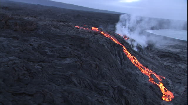 Steam rises from  flowing lava.