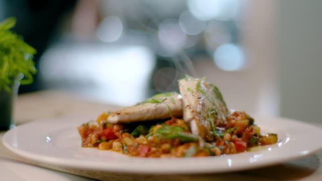 vídeos de stock, filmes e b-roll de o vapor sobe de peixes e legumes recém-cozidos - prato