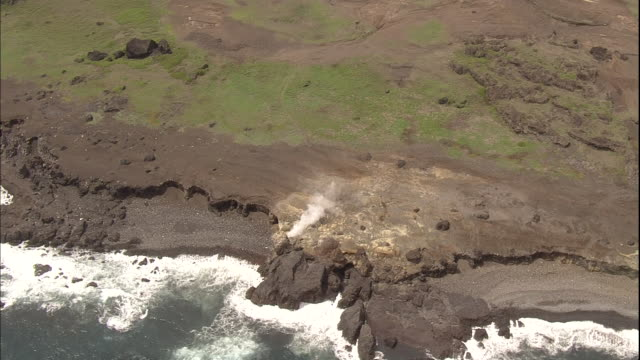steam rises from fumaroles near a rocky beach on iwo jima island, japan. - iwo jima island stock videos & royalty-free footage
