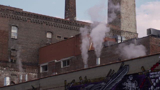 Steam rises from multiple vents on top of Brooklyn rooftop.