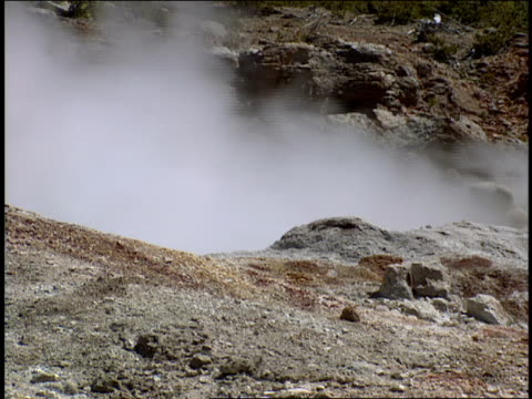 steam rises from rocky terrain at yellowstone national park. - 水の形態点の映像素材/bロール