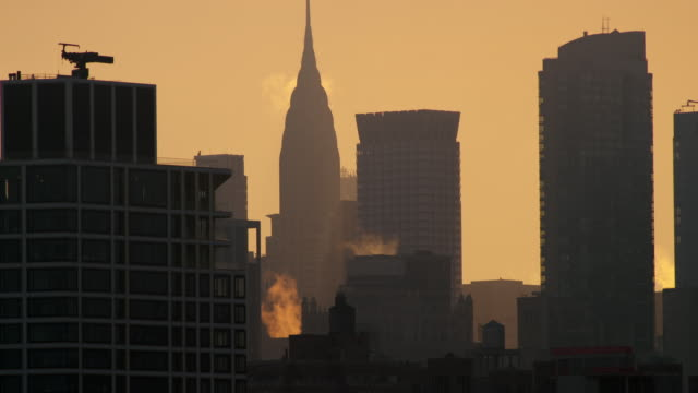 Steam rises from rooftops as the Chrysler Building stands tall against an orange sky during sunrise.