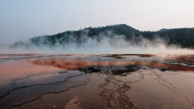 steam rises from the grand prismatic spring in the midway geyser basin of yellowstone national park. - geyser video stock e b–roll