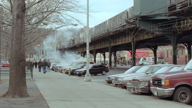 steam rises from the street below new york city's el train. - elevated train stock videos & royalty-free footage