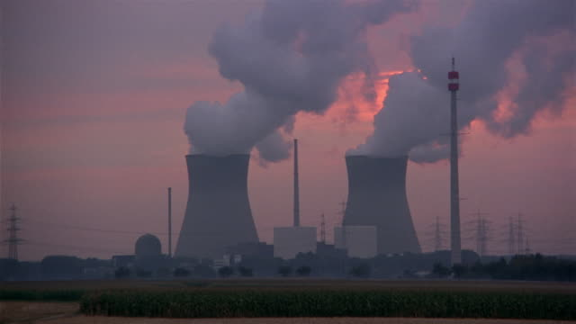 steam rises from two cooling towers at nuclear plant. - atomkraftwerk stock-videos und b-roll-filmmaterial