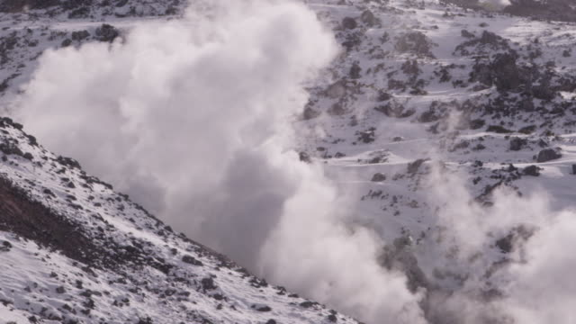 steam rises from volcanic vents on mountainside. - 噴気孔点の映像素材/bロール