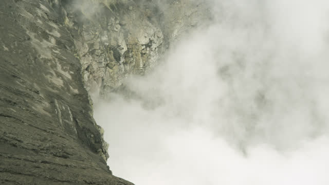 steam rises from volcano crater, java. - bromo crater stock videos & royalty-free footage