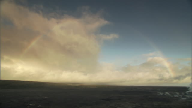steam rises in a pillar from a scrub desert as a full rainbow arches over top. - 虹点の映像素材/bロール