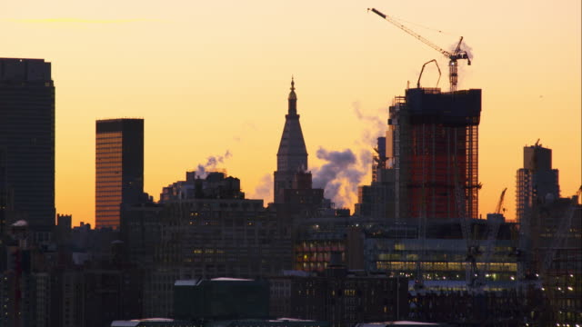 steam rises off the tops of a cluster of buildings in around the woolworth building in manhattan. - woolworth building stock videos & royalty-free footage