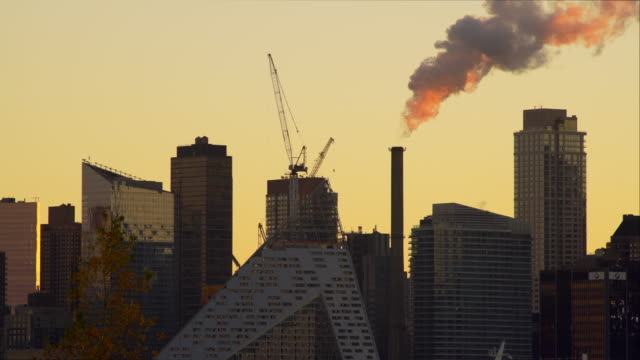 Steam rises out of a electric generation pipe early morning on the West Side of Manhattan.  The sky is a golden yellow.