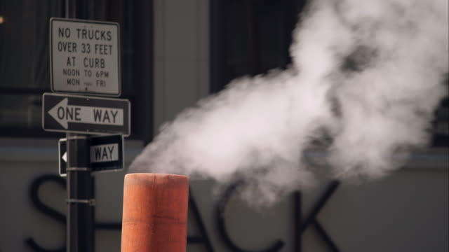 vídeos y material grabado en eventos de stock de steam rises up out of orange tube on new york city street. street signs out of focus in the background. - tapadera de cloaca