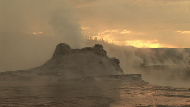 stockvideo's en b-roll-footage met ms, steam rising from castle geyser  at sunrise upper geyser basin, yellowstone national park, wyoming, usa - cross processen