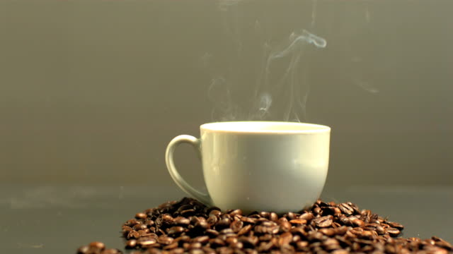 steam rising from cup of coffee on pile of coffee beans - cup stock videos & royalty-free footage