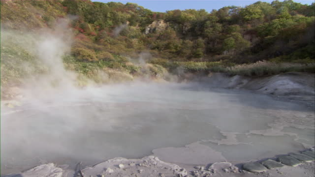 stockvideo's en b-roll-footage met ws steam rising from geothermal pool surrounded by forested hills / sapporo, hokkaido, japan - bron