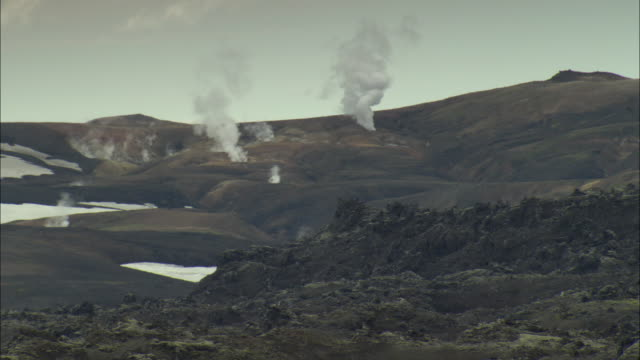 ws steam rising from geothermal vents in rugged, volcanic landscape with patches of snow under cloudy sky, lava rocks in foreground / selfoss, suourland, iceland - thermalquelle stock-videos und b-roll-filmmaterial