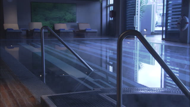 ms steam rising from indoor pool, lounge chairs in distance along with patio, woolloomooloo, new south wales - lido stock videos & royalty-free footage