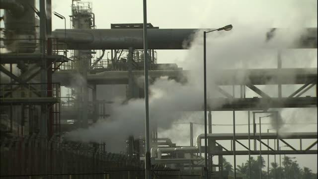vídeos de stock e filmes b-roll de steam rising from machinery at petrochemical plant - fábrica petroquímica