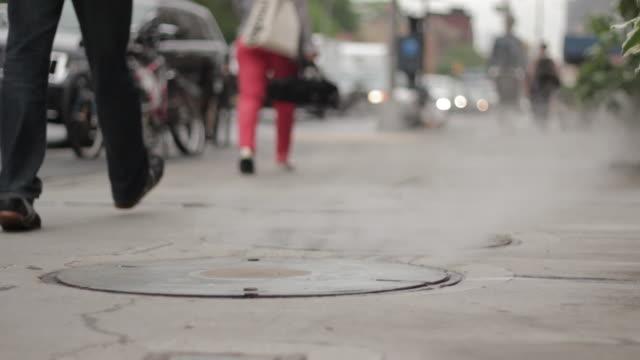 Steam rising from sidewalk manhole cover